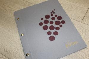livre de cave en papier gris et bordeaux avec grappe de raisins découpée au laser sur la couverture
